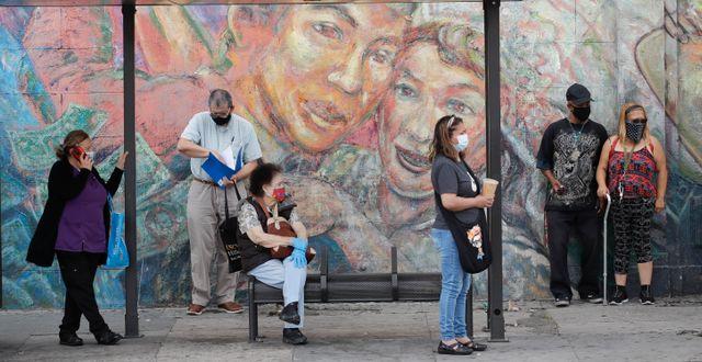 Människor vid en busstation i Los Angeles på måndagen.  Marcio Jose Sanchez / TT NYHETSBYRÅN