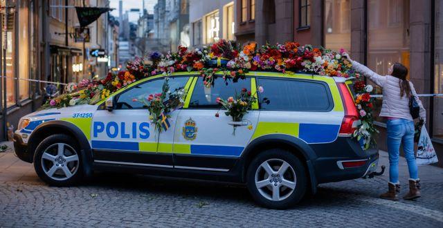 En kvinna lägga blommor på polisbil i centrala Stockholm. Markus Schreiber / TT / NTB Scanpix