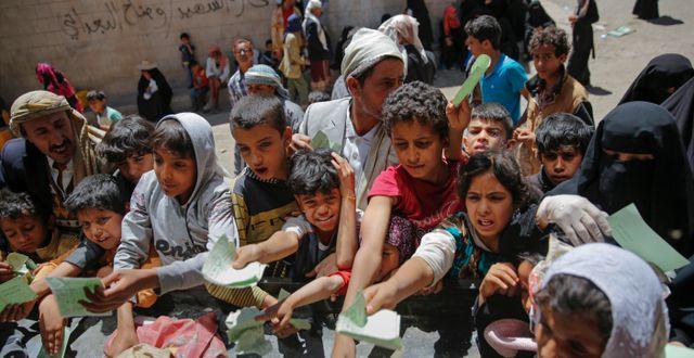 Jemeniter håller fram dokument för att få ta del av en matranson.  Hani Mohammed / TT / NTB Scanpix