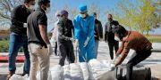 Människor i skyddsutrustning flyttar kroppen efter en person  Ebrahim Noroozi / TT NYHETSBYRÅN