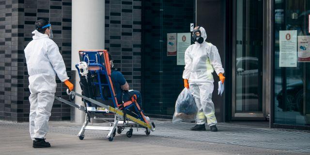 Personal iklädda skyddskläder hjälper en patient sittandes på en bår in på Karolinska sjukhuset i Solna. Anders Wiklund/TT / TT NYHETSBYRÅN