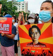 Demonstranter med Aung San Suu Kyis porträtt. TT NYHETSBYRÅN