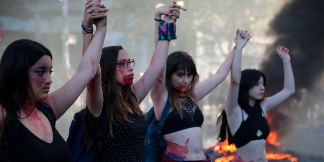 Kvinnor täckta i rött bläck demonstrerar i Santiago, Chile.  Rodrigo Abd / TT NYHETSBYRÅN