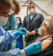 Jens Spahn (till höger) ser på när en kvinna får en vaccindos i Berlin.  Michael Kappeler / TT NYHETSBYRÅN
