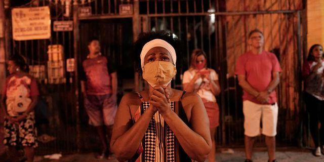 Kvinna iförd ansiktsmask ber till Gud i Brasilien.  Silvia Izquierdo / TT NYHETSBYRÅN