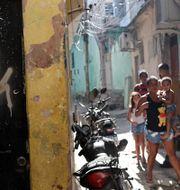 Boende i Jacarezinho bredvid en dörr med skotthål. Minst 25 personer dödades.  Silvia Izquierdo / TT NYHETSBYRÅN