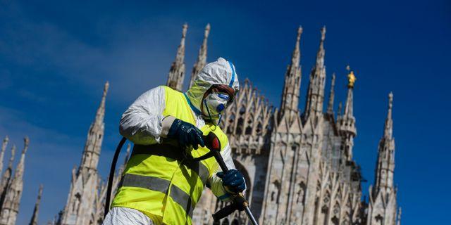 Hälsoarbetare sanerar Piazza Duomo i italienska Milano. PIERO CRUCIATTI / TT NYHETSBYRÅN