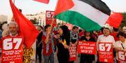 Demonstranter håller upp en palestinsk flagga under en protest mot Eurovision i Tel Aviv den 14 maj.  MENAHEM KAHANA / AFP