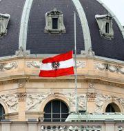 Österrikes flagga på halv stång utanför en byggnad i Wien.  Matthias Schrader / TT NYHETSBYRÅN