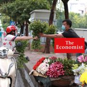 A seller hands flowers to a customer, both wearing face masks, in Hanoi, Vietnam. AP Photo/Hau Dinh