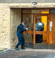 Poliser vid porten till familjens bostad i Haninge.  Claudio Bresciani / TT / TT NYHETSBYRÅN