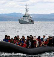 En flyktingbåt och en båt från Frontex utanför grekiska ön Lesbos Michael Varaklas / TT NYHETSBYRÅN