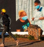 En pojke som går förbi en väggmålning i Sydafrika. Themba Hadebe / TT NYHETSBYRÅN