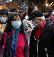 Människor med munskydd på Taipeis gator. Chiang Ying-ying / TT NYHETSBYRÅN