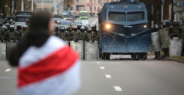 En demonstrant står framför kravallpolisen som spärrar av en gata.  TT NYHETSBYRÅN