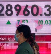 Två kvinnor går utanför Hong Kong Stock Exchange.  Vincent Yu / TT NYHETSBYRÅN