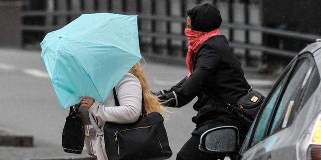 En kvinna med paraply i blåsten/arkiv.  Johan Nilsson/TT / TT NYHETSBYRÅN