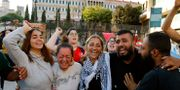 Regeringskritiska demonstranter jublar utanför regeringsbyggnaden i Beirut efter att premiärministern meddelat sin avgång. Bilal Hussein / TT NYHETSBYRÅN
