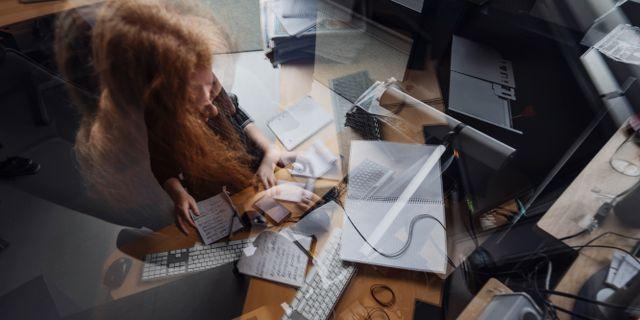Stressad kvinna vid skrivbord.  Stina Stjernkvist/TT / TT NYHETSBYRÅN