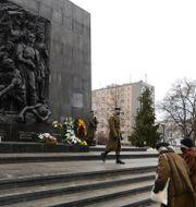 Besökare lämnar kransar vid en minnesplats i Polens huvudstad. Czarek Sokolowski / TT NYHETSBYRÅN