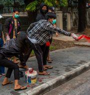 Demonstranter kastar röd färg på gatorna i Rangoon i Myanmar.  TT NYHETSBYRÅN