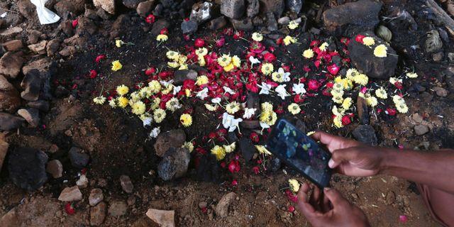 En förbipasserande fotograferar platsen där en 27-årig kvinnas kropp hittades.  Mahesh Kumar A / TT NYHETSBYRÅN