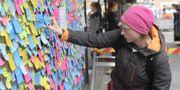 Maria Schwebke vid en minnestavla med meddealndet på post-itlappar till offren för lastbilsattacken på Drottninggatan. Anders Wiklund/TT / TT NYHETSBYRÅN