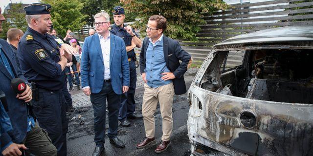 Moderatledaren Ulf Kristersson (th) i samtal med Dan Windt (tv), chef för lokalpolisområde Storgöteborg Syd, och Jonas Ransgård (M) under ett besök på Frölunda torg efter nattens bilbränder. Adam Ihse/TT / TT NYHETSBYRÅN