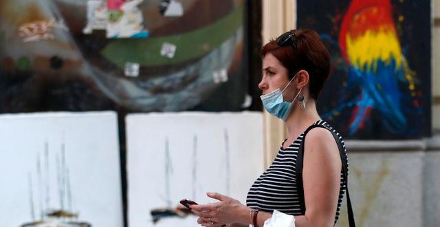 En kvinna bär en ansiktsmask i Belgrad på torsdagen, dagen innan vissa restriktioner återinfördes Darko Vojinovic / TT NYHETSBYRÅN