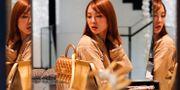 Kvinna tittar på väskor i en lyxbutik i Hongkong. Jorge Silva / TT NYHETSBYRÅN