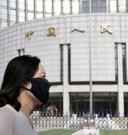 Arkivbild: En kvinna passerar utanför PBOC:s huvudkontor i Peking Jason Lee / TT NYHETSBYRÅN