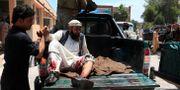 En skadad man får hjälp att hoppa av en bil efter dagens attack mot en begravningsceremoni. PARWIZ / TT NYHETSBYRÅN