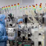 In this May 14, 2020, file photo, employees wearing protective equipment work at a semiconductor production facility for Renesas Electronics during a government organized tour for journalists in Beijing. Mark Schiefelbein / TT NYHETSBYRÅN
