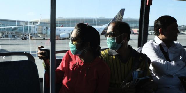 Människor bär ansiktsmasker på flygplatsen i Bombay den 10 mars. TT