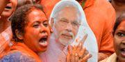 En anhängare till BJP poserar med en bild på Modi. DIPTENDU DUTTA / AFP