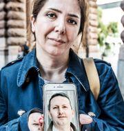Vida Mehrannia håller upp en bild av sin man. Tomas Oneborg/SvD/TT / TT NYHETSBYRÅN