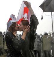 Två personer kysser varandra nära Självständighetspalatset i Minsk. TT NYHETSBYRÅN