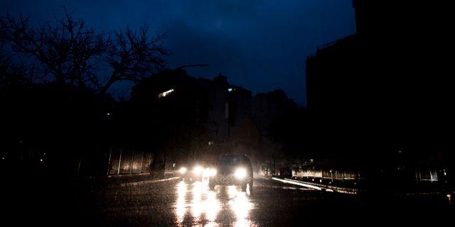 Bilar kör genom de mörka gatorna. Tomas F. Cuesta / TT NYHETSBYRÅN