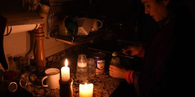 En kvinna har tänt levande ljus i sitt kök. MIGUEL ROJO / AFP
