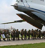 Ryska fallskärmsjägare går ombord på ett flygplan. TT NYHETSBYRÅN
