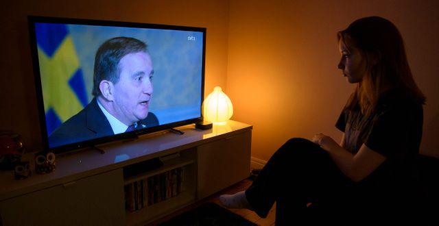 En kvinna ser på när statsminister Stefan Löfven (S) håller ett tal till nationen med anledning av coronapandemin. Jessica Gow/TT / TT NYHETSBYRÅN