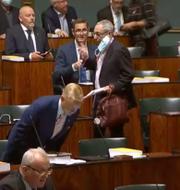 En av ledamöterna tar av sig sitt munskydd.  Eduskunta/Riksdagen