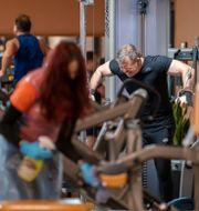 Illustrationsbild. En medarbetare på ett gym rengör utrustningen.  Joe Giddens / TT NYHETSBYRÅN