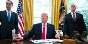 Donald Trump omgiven av finansminister Steven Mnuchin och vice president Mike Pence. Alex Brandon / TT NYHETSBYRÅN