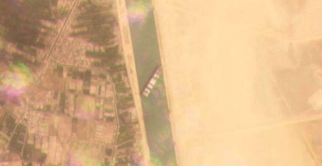 Satellitbild från Planet Labs visar att fraktbjässen Ever Given sitter fast tvärs över kanalen.  Planet Labs Inc. / TT NYHETSBYRÅN