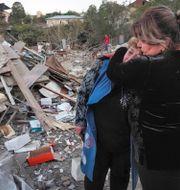 Grannar i Nagorno-Karabach tröstar varandra vid ett förstört hus. TT NYHETSBYRÅN