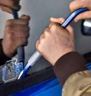 En person bryter sig in i en bil.  Claudio Bresciani / TT / TT NYHETSBYRÅN