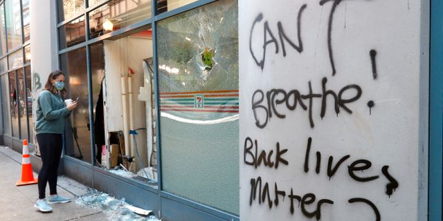 En fotgängare kollar in i en vandaliserad affär tidigt på söndagsmorgonen. Charles Rex Arbogast / TT NYHETSBYRÅN