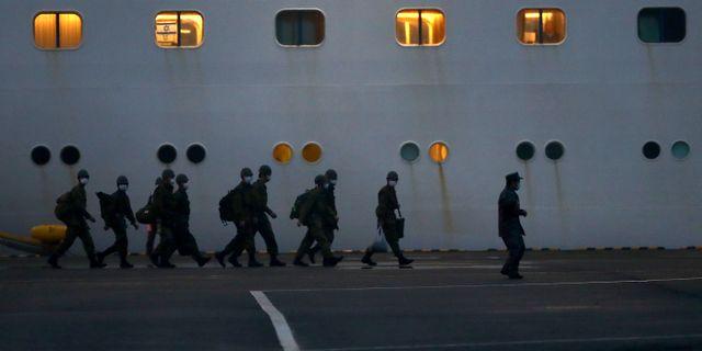 Japansk trupp utanför kryssningsfartyget Diamond Princess. BEHROUZ MEHRI / AFP