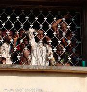 Människor kollar ut genom fönstret på centret innan de fritogs under måndagen i staden Ibadan i Nigeria. NIGERIA POLICE / TT NYHETSBYRÅN